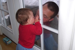 Kissing Daddy through the door.